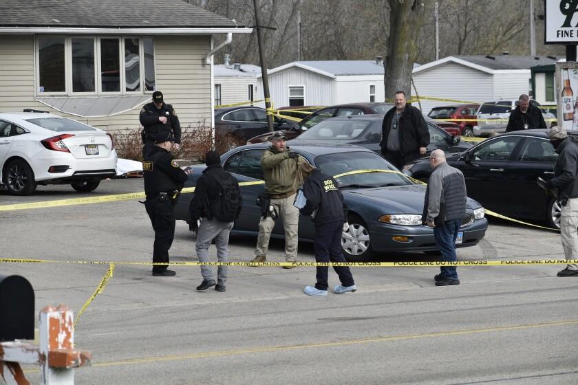 Investigators inside an area blocked off by crime scene tape