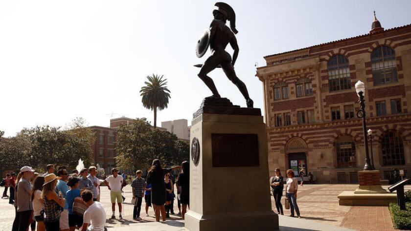 """La gente se reúne alrededor de la estatua de """"Tommy Troya"""", en el campus de USC en Los Ángeles (Al Seib / Los Angeles Times)"""
