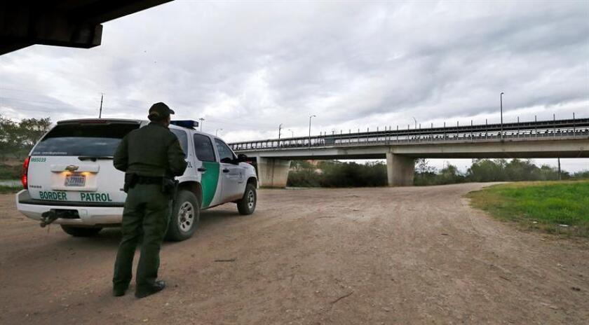 Un agente de la Patrulla Fronteriza observa desde una carretera frente a México, mientras que personas se alinean en el puente de un puerto de entrada a través del Río Grande para ingresar a los Estados Unidos cerca de McAllen, Texas, EE. UU., el 23 de enero de 2019. EFE/Archivo