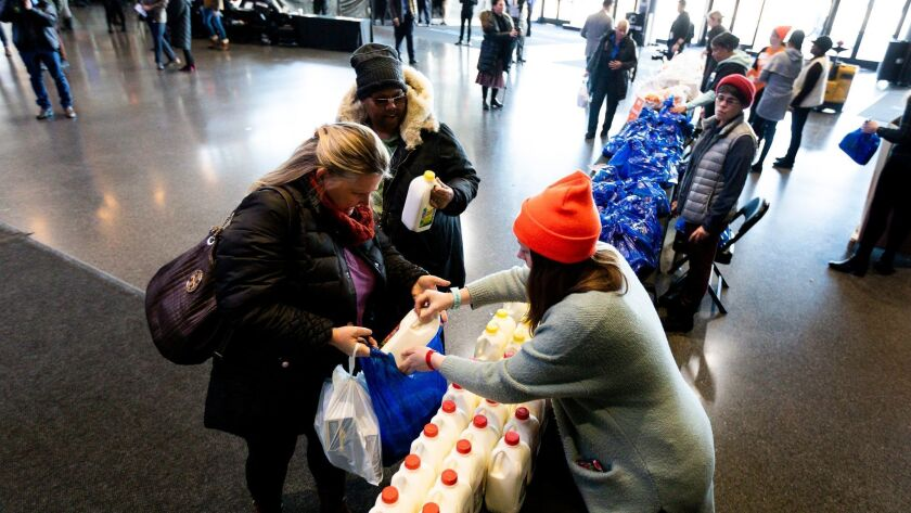 Unpaid federal workers collect collect milk and food at a food donation site set up by the Food Bank of NYC at the Barclays Center in Brooklyn, N.Y.