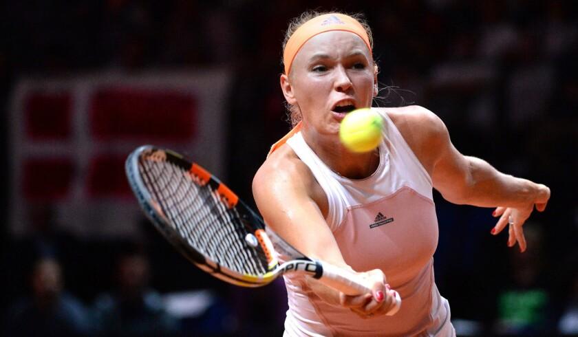 Caroline Wozniacki volleys a shot against Simona Halep during their semifinal match at the Porsche Grand Prix on Saturday.