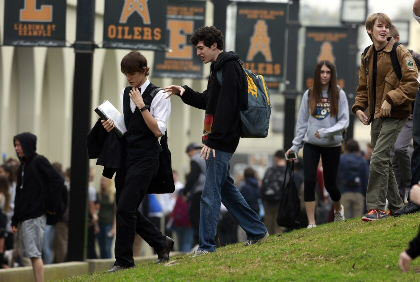 Students go about their business at Huntington Beach High School after being warned that one person on campus was diagnosed with measles in January.