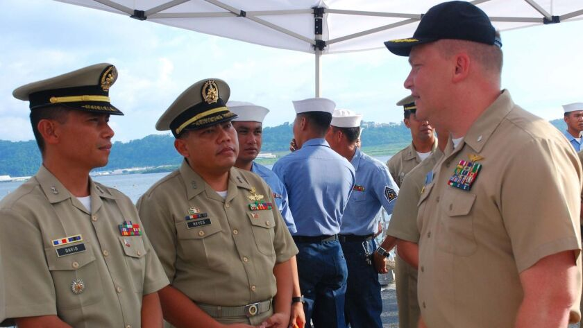 Cmdr. Troy Amundson, right, speaks with members of the Philippine Navy before a closing ceremony for a training mission aboard the guided-missile destroyer Halsey in 2010.