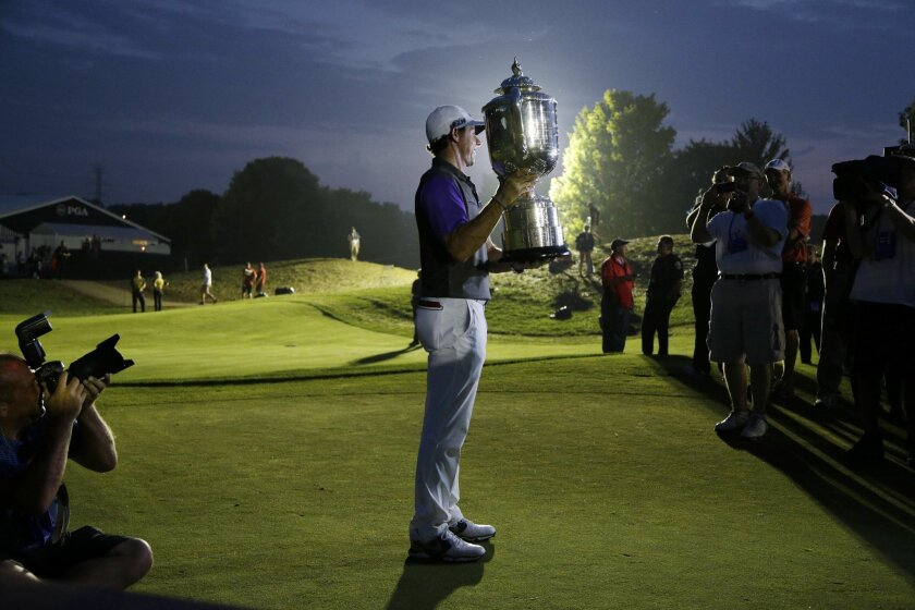 Rory McIlroy, of Northern Ireland, holds up the Wanamaker Trophy after winning the PGA Championship golf tournament at Valhalla Golf Club on Sunday, Aug. 10, 2014, in Louisville, Ky. (AP Photo/John Locher)