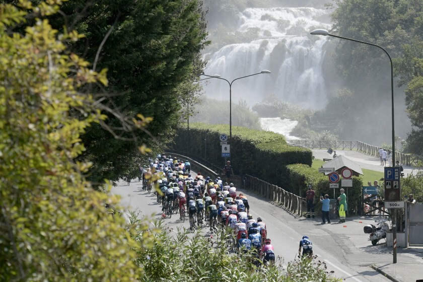 The pack of cyclists ride past the Marmore Waterfalls during the fourth stage of the Tirreno Adriatico cycling race, from Terni to Cascia, Italy, Thursday, Sept. 10, 2020. (Marco Alpozzi/LaPresse via AP)