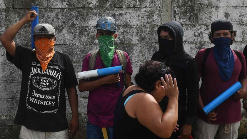 """A neighborhood resident walks past a group of members of the """"April 19"""" movement, after leaders of the movement held a news conference in Masaya, Nicaragua, on June 18, 2018."""