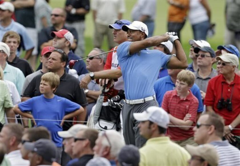 Tiger Woods tees off on the third hole during the second round of the Bridgestone Invitational golf tournament Friday, Aug. 2, 2013 at Firestone Country Club in Akron, Ohio. Woods tied a course record with a round of 9-under par 61 and leads the tournament at 13-under. (AP Photo/Mark Duncan)