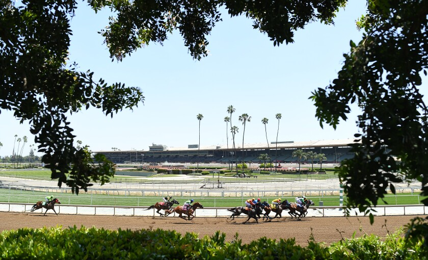 Horses race around the turn at Santa Anita Park during the COVID-19 pandemic.