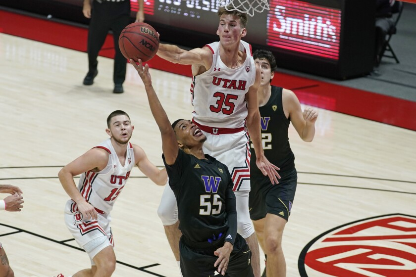 Utah center Branden Carlson (35) defends against Washington guard Quade Green (55) as he goes to the basket during the first half of an NCAA college basketball game Thursday, Dec. 3, 2020, in Salt Lake City. (AP Photo/Rick Bowmer)
