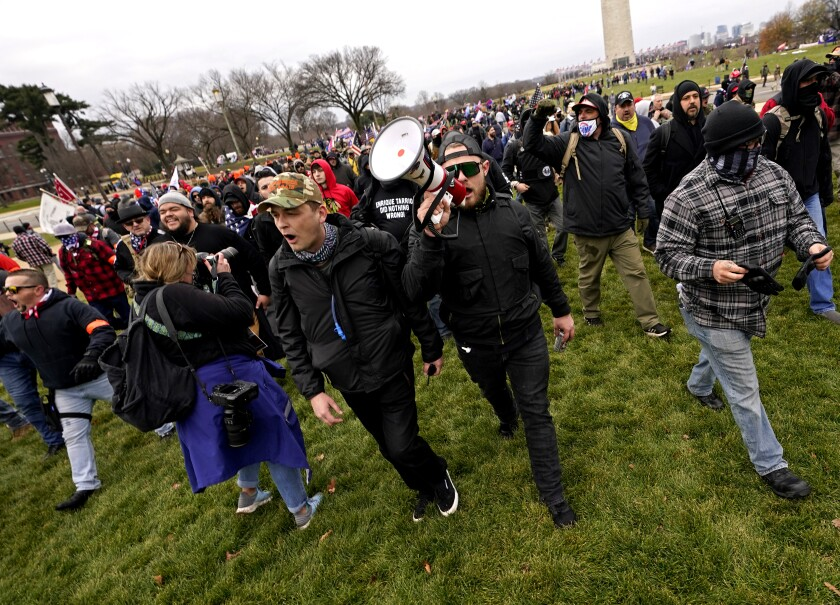 A man with a bullhorn leads a large group of men dressed in black across a lawn.