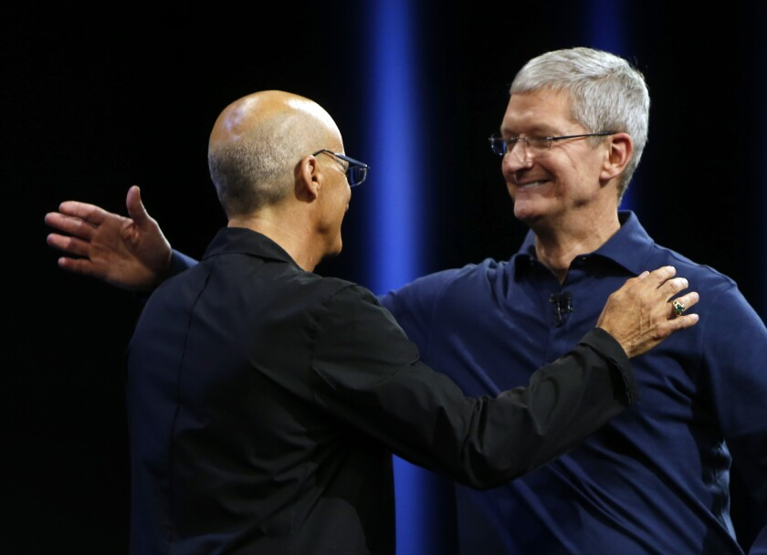 Apple CEO Tim Cook, right, hugs Jimmy Iovine, who appeared on stage to help introduce the new Apple Music, at the Worldwide Developers Conference on Monday, June 8, 2015, in San Francisco.