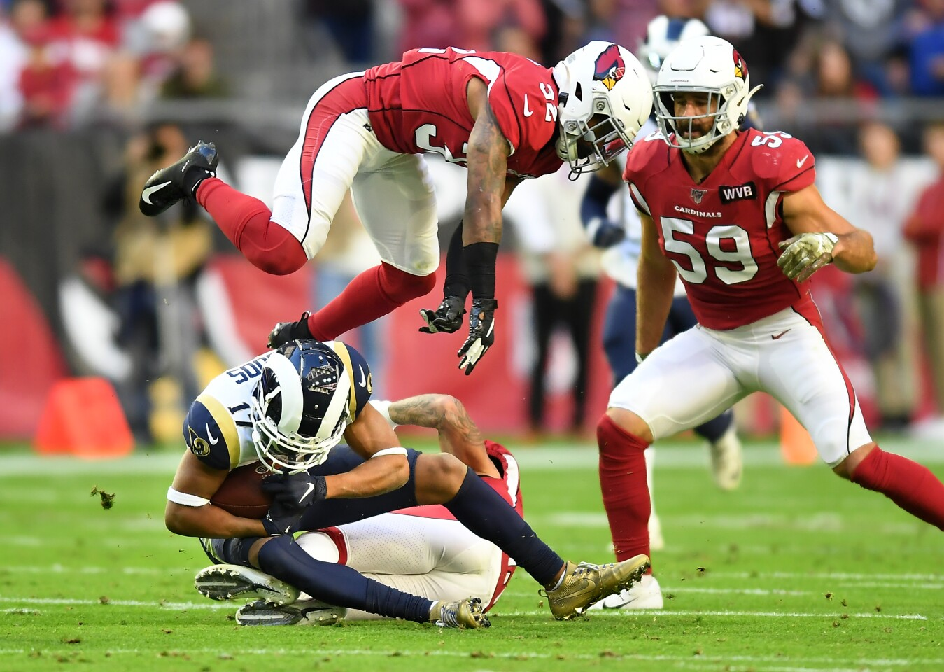Rams wide receiver Robert Woods makes a reception as Cardinals safety Budda Baker leaps over him in front of linebacker Joe Walker.