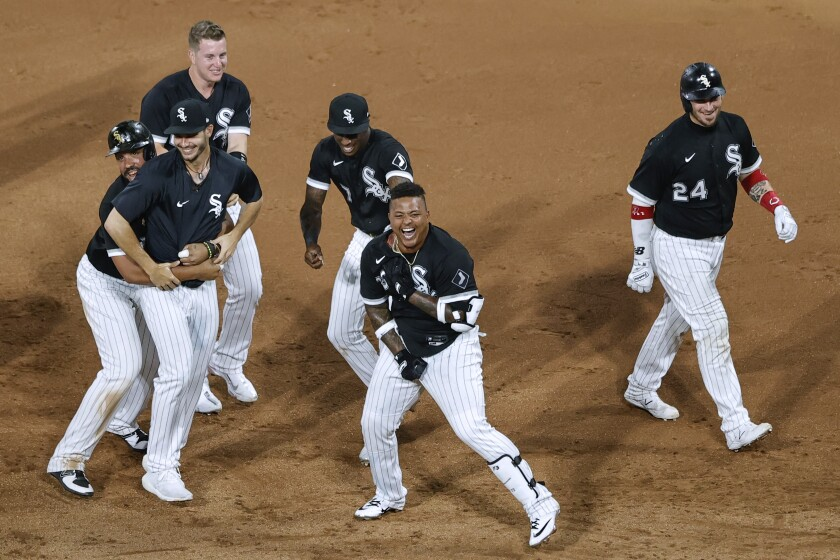 Chicago White Sox's Yermin Mercedes, front center, celebrates with teammates after hitting a single off Detroit Tigers relief pitcher Jose Cisnero to drive in the winning run during the ninth inning of a baseball game Friday, June 4, 2021, in Chicago. (AP Photo/Kamil Krzaczynski)