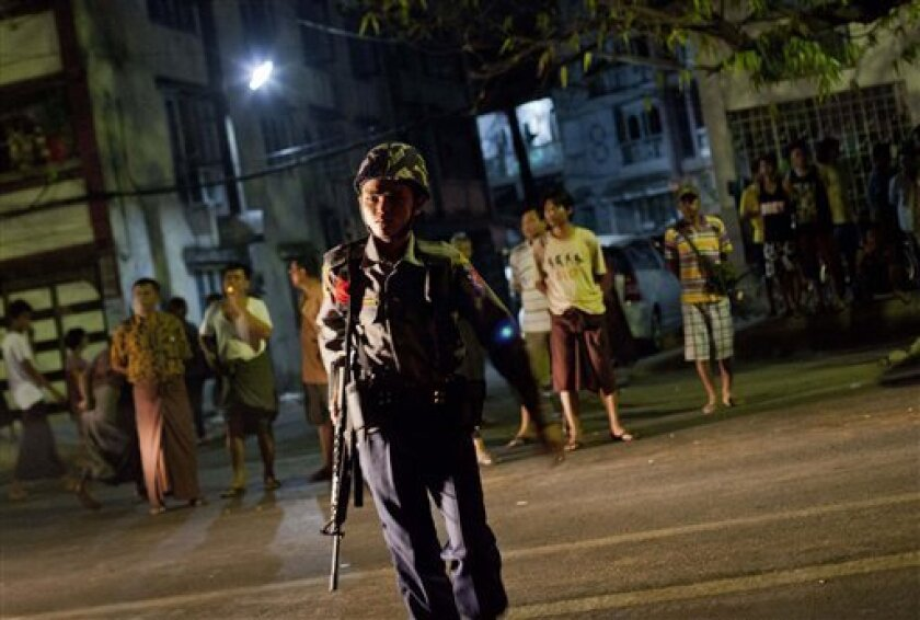 A Police officers patrols outside the mosque after a fire in Yangon, Myanmar, Tuesday, April 2, 2013. Police in Myanmar said 13 children died when an electrical fire broke out at the mosque in the country's largest city. (AP Photo/Gemunu Amarasinghe)
