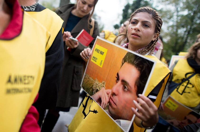 Ensaf Haidar, wife of the imprisoned Saudi Arabian blogger Raif Badawi, holds a poster of her husband while taking part in a demonstration in Vienna this month calling for his release.