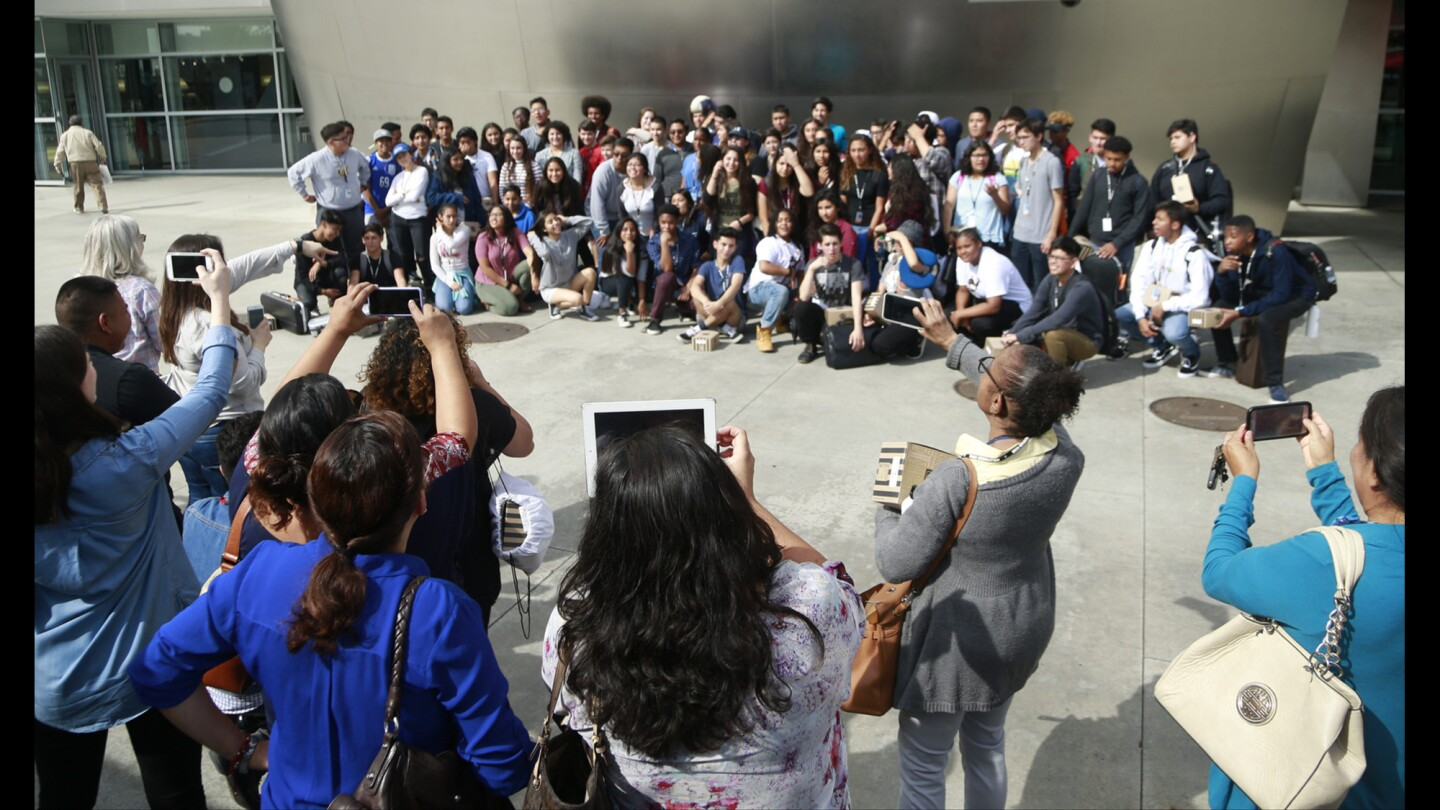 The Youth Orchestra of Los Angeles poses for group photos taken by family members.