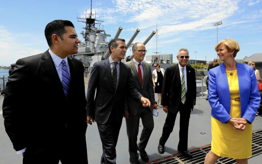 Long Beach Mayor Robert Garcia, left, Los Angeles Mayor Eric Garcetti, Labor Secretary Thomas E. Perez, Rep. Alan Lowenthal (D-Long Beach) and Rep. Janice Hahn (D-Los Angeles) walk to a news conference on the battleship Iowa in San Pedro.