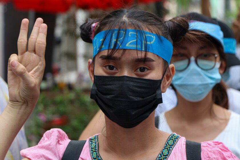 An anti-coup protester flashes the three-fingered salute while wearing a headband that reads R2P, which means Responsibility to Protect, during a gathering in Ahlone township in Yangon, Myanmar Monday, April 12, 2021. The protesters have called for foreign intervention to aid them under the doctrine of Responsibility to Protect, or R2P, devised to deal with matters such as genocide, war crimes, ethnic cleansing and crimes against humanity. (AP Photo)