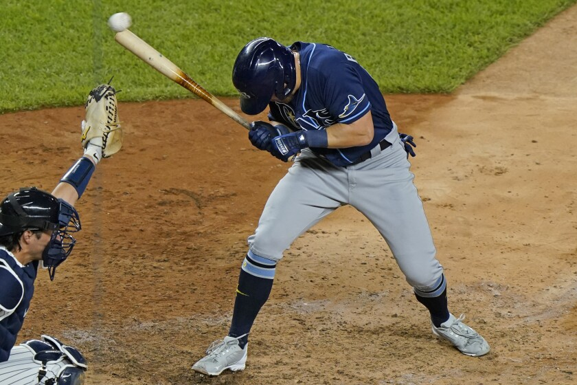 Tampa Bay Rays pinch-hitter Michael Brosseau ducks away from a pitch from New York Yankees reliever Aroldis Chapman during the ninth inning of a baseball game Tuesday, Sept. 1, 2020, at Yankee Stadium in New York, as catcher Kyle Higashioga reaches for the ball. (AP Photo/Kathy Willens)