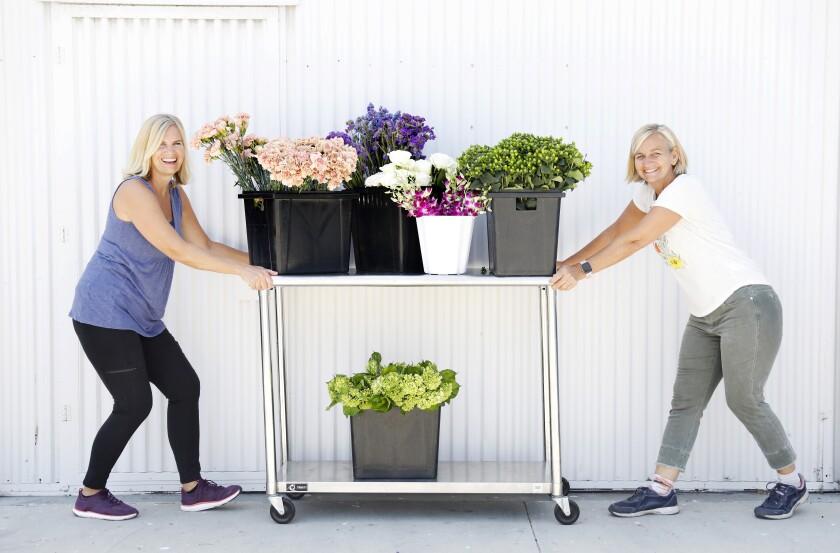 Los propietarios de Flower Duet, Kit Wertz y Casey Schwartz, empujan un carrito de flores