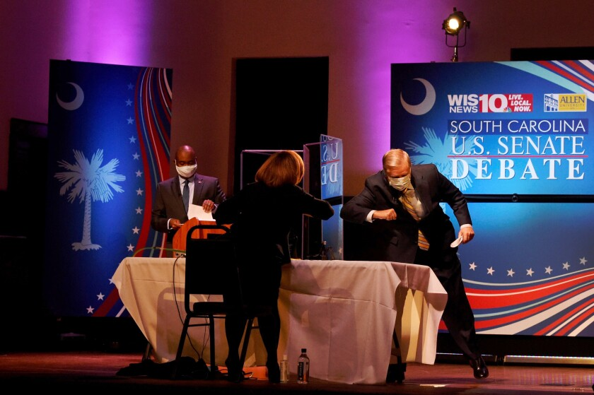 Sen. Lindsey Graham, right, gives moderator Judi Gatson an elbow bump after debating challenger Jaime Harrison.