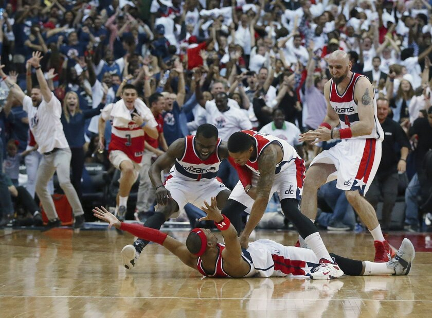 Washington Wizards players mob Paul Pierce on the floor after his game winning shot as time expired after Game 3 of the second round of the NBA basketball playoffs Saturday, May 9, 2015, in Washington. The Wizards won 103-101. (Curtis Compton/Atlanta Journal-Constitution via AP)  MARIETTA DAILY OUT
