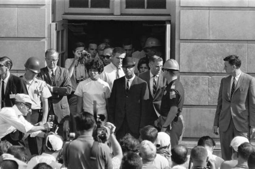 Vivian Malone and James A. Hood stand outside a doorway at the University of Alabama after registering for classes on June 11, 1963.