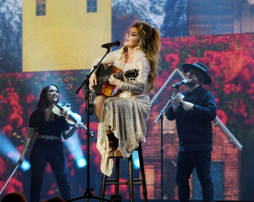 Shania Twain, sitting on a stool, plays the guitar and sings. Behind her are two background singers.