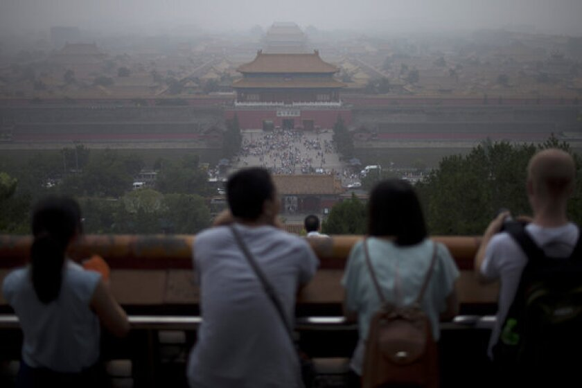 Tourists look at the Forbidden City from the top of Jinshan Hill on a hazy day in Beijing