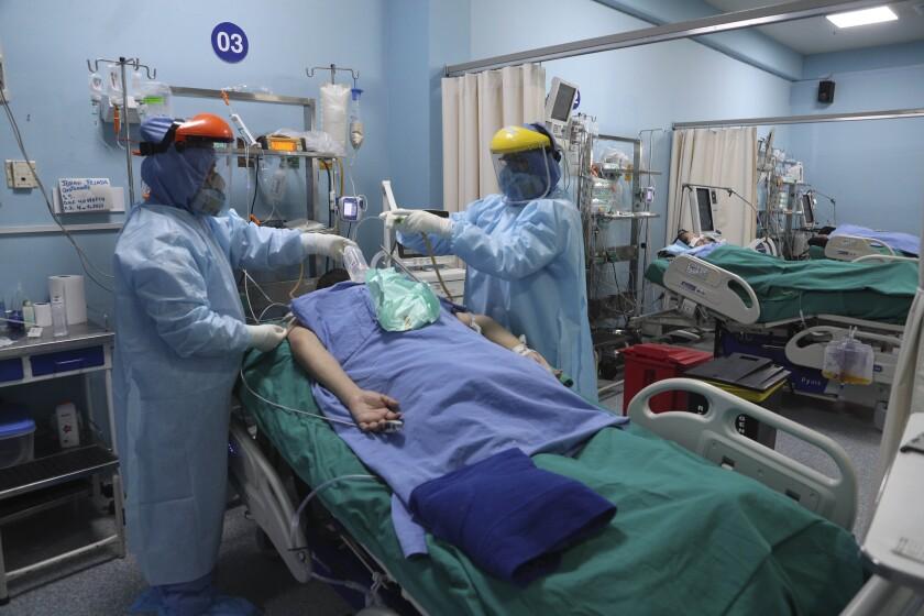 Trabajadores de salud atienden a un paciente dentro de la Unidad de Cuidados Intensivos por COVID-19