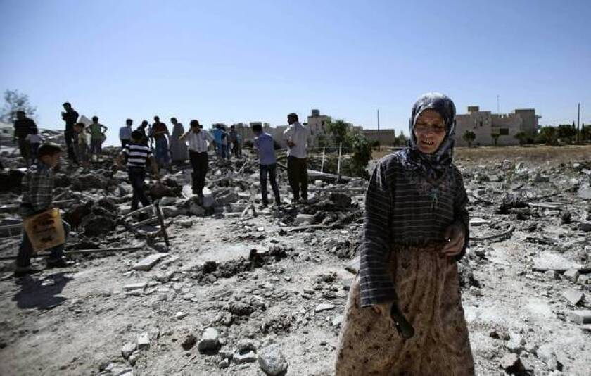 A woman in Azaz, Syria, looks at the rubble of a house destroyed by government shelling this week.
