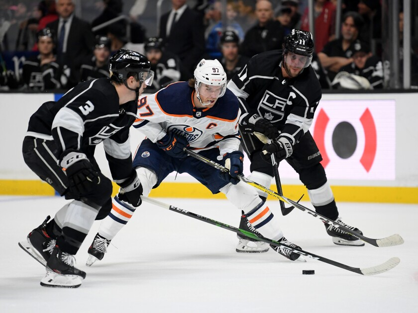 Edmonton Oilers forward Connor McDavid handles the puck between Kings defenseman Matt Roy, left, and forward Anze Kopitar during the Kings' 4-2 loss Sunday.
