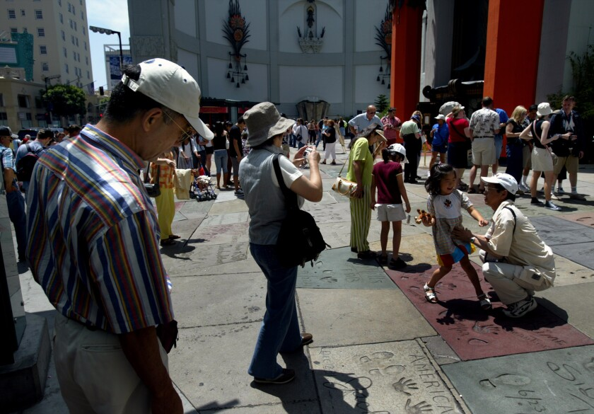 Tourists swarm the Chinese Theatre in Hollywood on June 24, 2004.