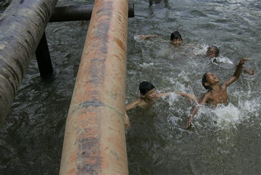 Children play in a river where oil pipes run above the surface in Ecuador's Sucumbios province, Aug. 4, 2008.  Ecuador's President Rafael Correa has sided squarely with the 30,000 plaintiffs, Indians and colonists, in a class-action suit, dubbed an Amazon Chernobyl by environmentalists, over the sl