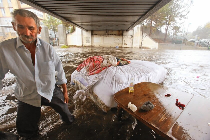 The bed of Felipe Flores Lopez, 59, floats away as he loses his homeless encampment when rainwater floods a section of Avenue 26 under the Cypress Park/Lincoln Heights Gold Line Station in Lincoln Heights.
