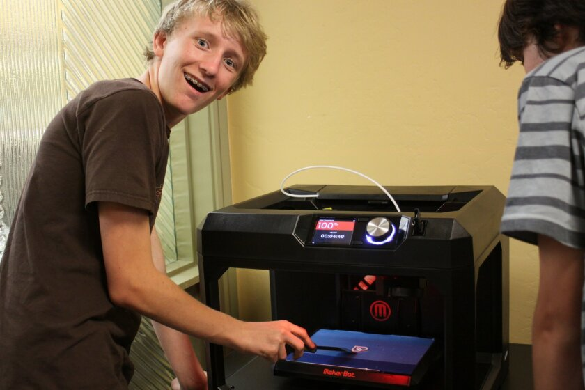 Teddy Dykstra, a La Jolla High School student, is elated to take a freshly printed paperclip from the 3-D printer at La Jolla Library.
