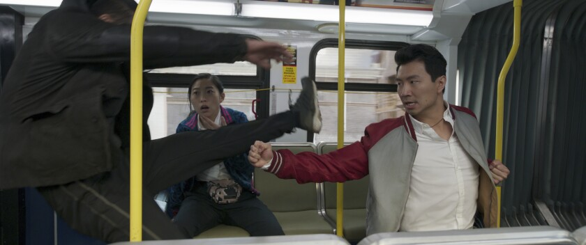 a woman watching a man punch another man in a bus
