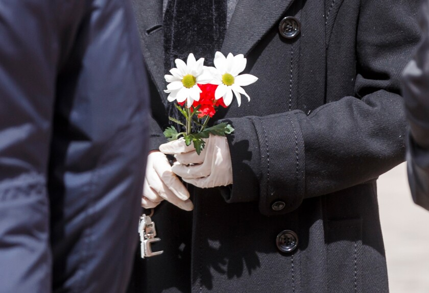 A man wearing gloves holds flowers during the burial service of a man who died of the new coronavirus, at the South Municipal cemetery in Madrid on March 23.