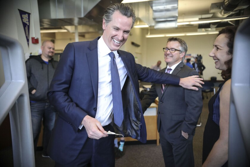 Gov. Gavin Newsom shares a moment with Principal Scott Irwin after a tour of Dana Middle School in Point Loma on Feb. 28.