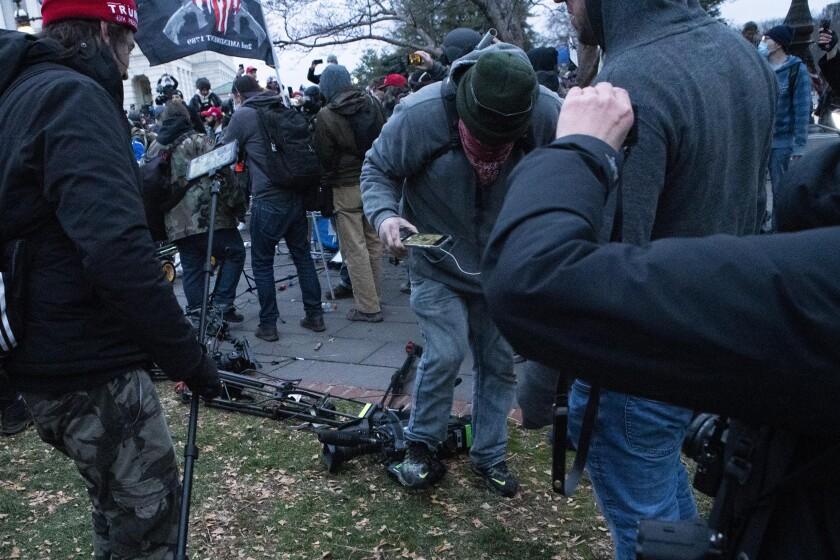 Demonstrators breaking TV equipment.