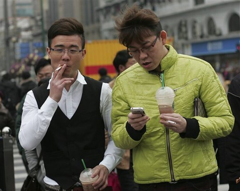 Pedestrian smoke on a street Tuesday, March 2, 2010 in Shanghai, China. Restaurants and office buildings in China's commercial capital Shanghai are scrambling to set up nonsmoking areas as the city bans lighting up in indoor public spaces ahead of the World Expo. There is rising awareness of the health risks of smoking in China, by far the world's biggest tobacco-consuming country, and this modern city of 20 million is cleaning up its act as it prepares to host the Expo, which begins May 1. (AP Photo)