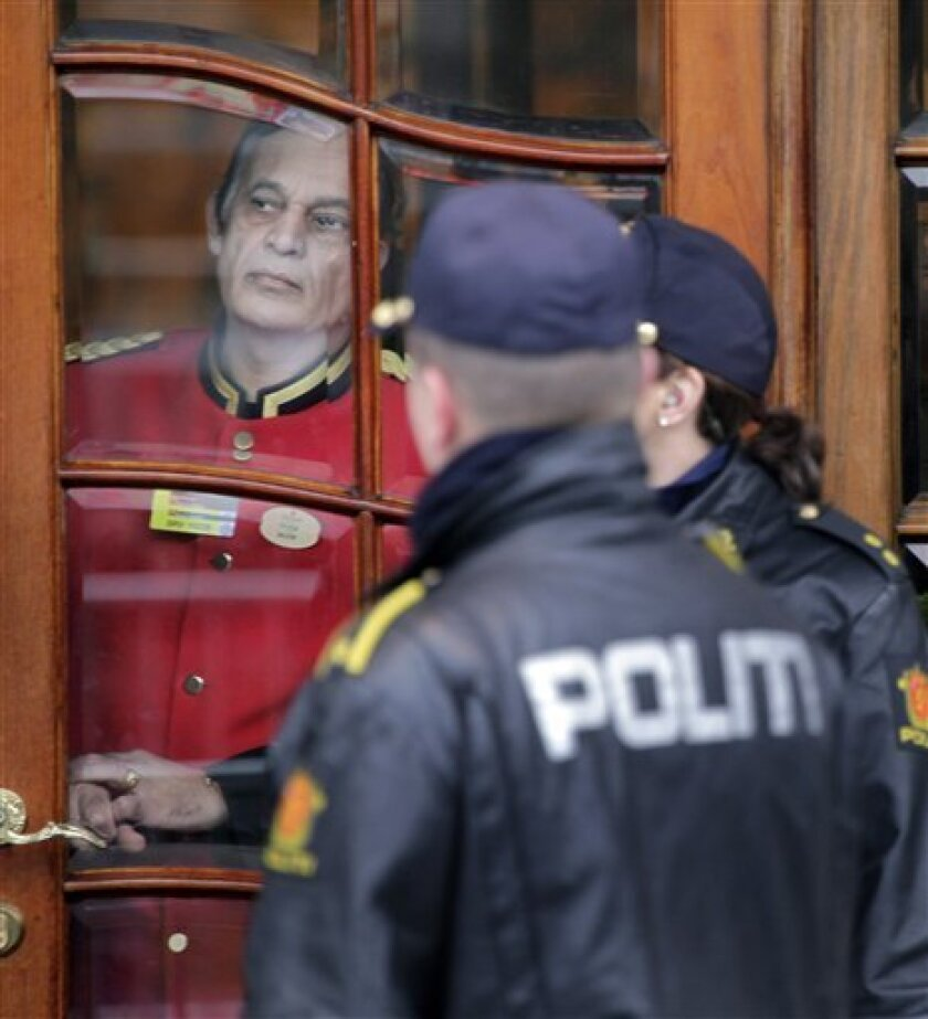 A hotel worker peers out the door past police at the hotel in Oslo, Norway where Nobel Peace laureate Barack Obama will be staying Wednesday Dec. 9, 2009. Obama will receive the prize on Thursday in Oslo. (AP Photo/John McConnico)