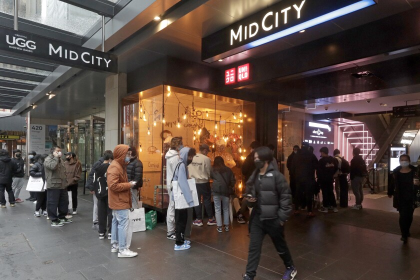 Varios clientes se forman para entrar a una tienda en el principal distrito comercial