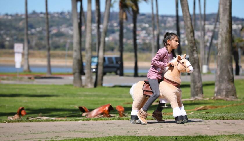 A kindergartner rides her toy horse in San Diego