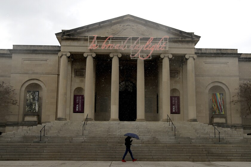 A man holding an umbrella walks past the Baltimore Museum of Art on a rainy, cloudy day.