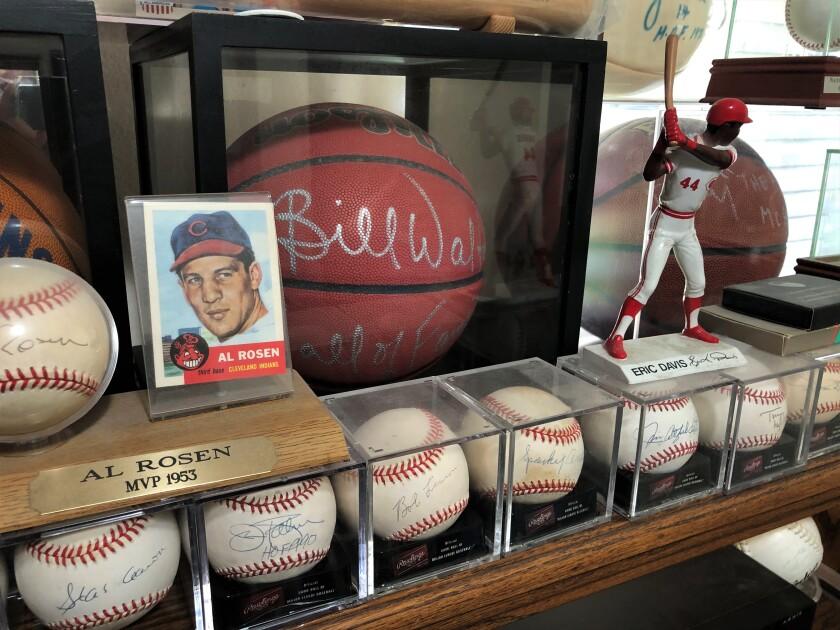 An Al Rosen baseball card and an Eric Davis figure sit atop a row of autographed baseballs at Rick Obrand's.