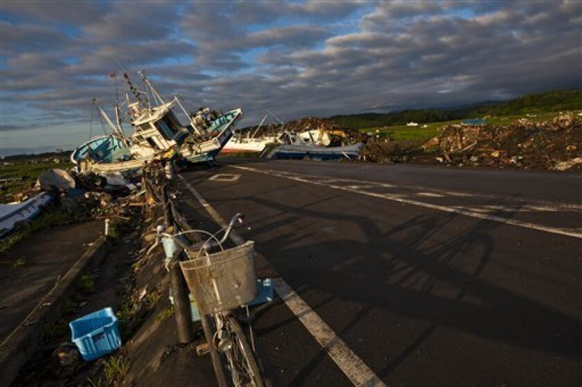 In this July 24, 2011 photo, an abandoned bicycle rests on a road partially blocked by ships that washed ashore in the town of Namie, inside the 20-kilometer (12-mile) exclusion zone around the Fukushima Dai-ichi nuclear plant, in northeastern Japan. A year after a tsunami crippled the plant and ca