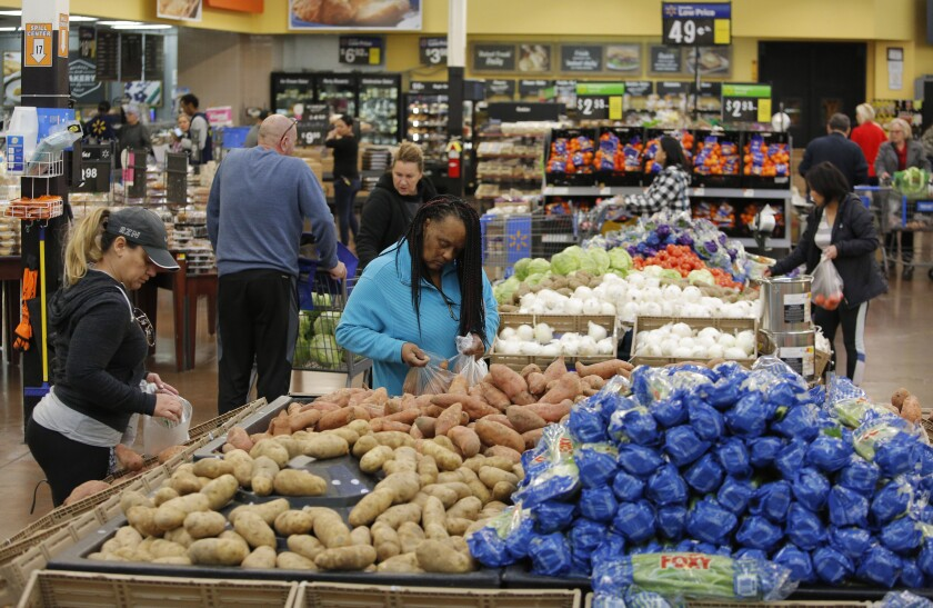 FILE - In this Nov. 27, 2019, file photo people shop for food the day before the Thanksgiving holiday at a Walmart Supercenter in Las Vegas. U.S. consumer prices increased slightly last month, driven higher by more expensive food. The Labor Department said Wednesday, March 11, 2020, that the consumer price index ticked up 0.1% last month, matching its January increase. (AP Photo/John Locher, File)