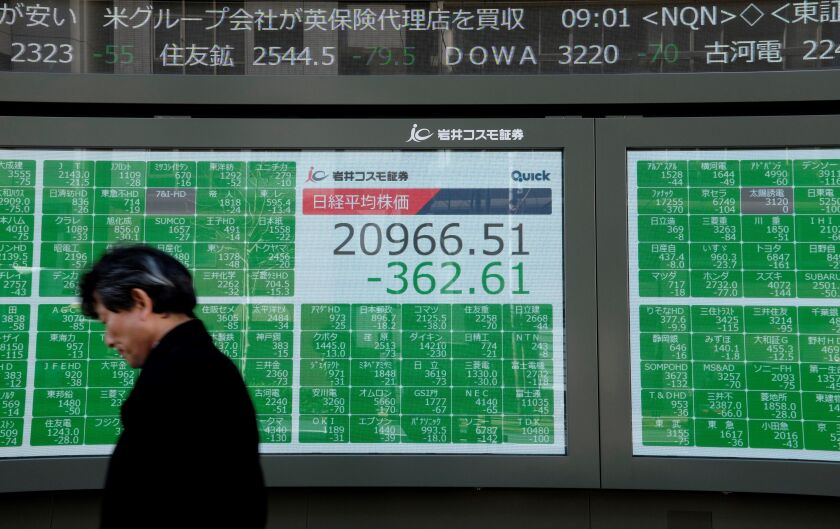 A man walks past an electronic board at the Tokyo Stock Exchange on Friday.