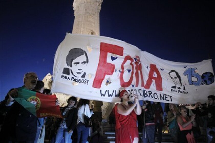 """People holding a banner with the faces of Portugal's Prime Minister Pedro Passos Coelho and former Foreign Minister Paulo Portas and that reads in Portuguese: """"Out"""" shout slogans against the government in Lisbon, Tuesday, July 2, 2013. Portugal's Prime Minister defied calls to resign Tuesday after his coalition government was rocked by a second Cabinet resignation in as many days over tough budget cuts that have sharply reduced living standards in one of the poorest countries that uses the euro."""